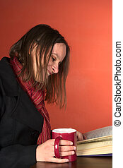 Young Caucasian woman reading a book and drinking tea at a table (Selective Focus, Focus on the right eye)