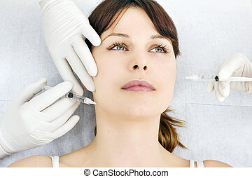 young caucasian woman receiving an injection of botox from a...