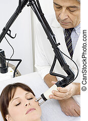 young caucasian woman receiving electrostimulation lifting from a male doctor