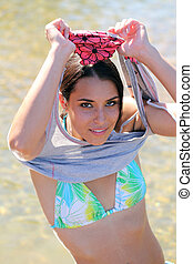 Young caucasian woman removing shirt bikini beneath