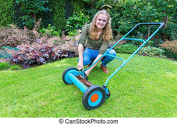 Young caucasian woman reparing lawn mower in garden