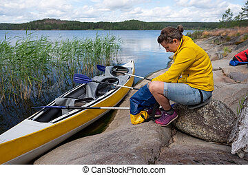 Young caucasian woman resting on riverside after kayaking.