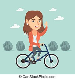 Young caucasian woman riding bicycle in the park.