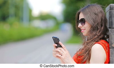 Young caucasian woman sending message and listen music outdoor at european city. Beautiful girl in sunglasses sitting on wooden bench using smartphone
