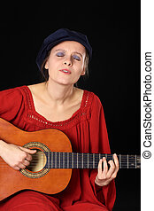 Young Caucasian woman singing and playing the guitar with eyes closed (Selective Focus, Focus on the face)