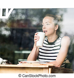 Young caucasian woman sitting alone in coffee shop thoughtfully leaning on her hand, looking trough the window