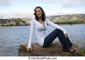 Young caucasian woman sitting on rock at lake