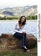 Young Caucasian Woman Sitting On Rock Lakeside