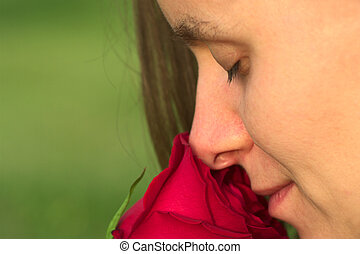 Young Caucasian woman smelling at a red rose with closed eyes (Very Shallow Depth of Field)