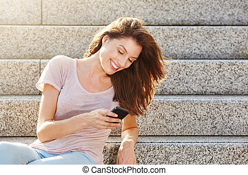 Young caucasian woman smiling and looking at mobile phone