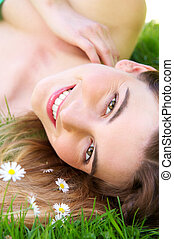 Young caucasian woman smiling outdoors with flowers