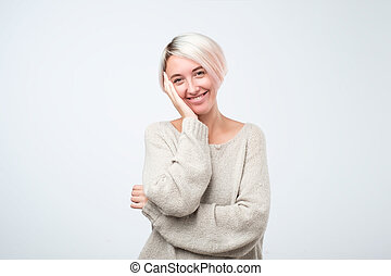 Young caucasian woman smiling standing on gray background