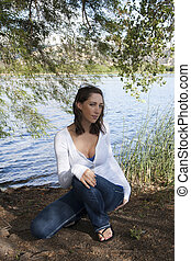 Young caucasian woman squatting under tree lake