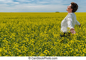 Young caucasian woman standing with arms raised in a canola field in bloom