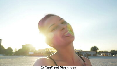 Young caucasian woman taking video call and making funny faces on a beach