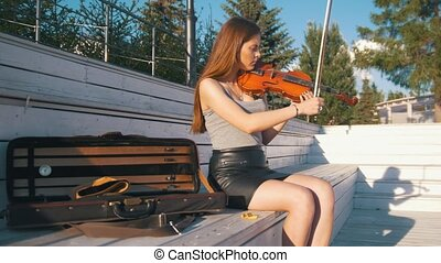Young caucasian woman tunes her violin sitting on the bench...