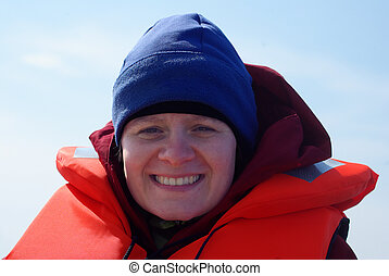 Young caucasian woman wearing a lifejacket with a red jacket below, with a blue cap on the head on a clear and sunny day
