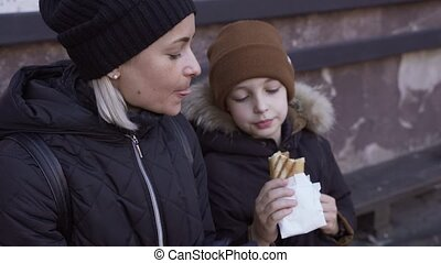 Young caucasian woman with boy eating hot dog and drinking coffee outdoor at winter time