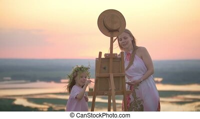 Young caucasian woman with daughter painting nature on the...