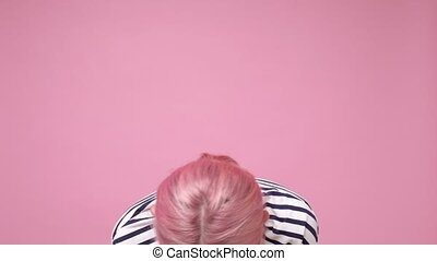 Young caucasian woman with dyed pink hair laughing on funny ...