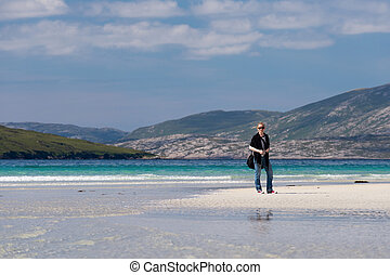 Young Caucassian woman enjoying holiday on a white sandy beach with turquoise water, Luskentyre, Isle of Harris, Scotland