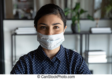 Head shot close up young cautious indian ethnicity businesswoman wears breath protective facemask looking at camera. Smart female employee worker protecting from corona virus infection indoors.