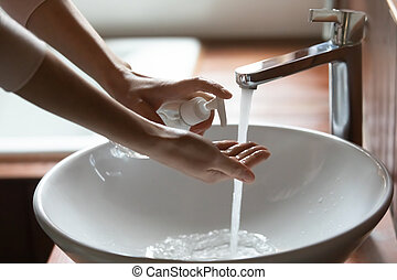 Side view young cautious woman applying antibacterial soap on hands, doing regular sanitizing routine in bathroom at home, preventing spreading covid 19 corona virus infection, healthcare concept.