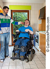 Young spastic male infantile cerebral palsy patient caused by birth complications sitting in a multifunctional wheelchair listening to music on headphones aided by a carer smiling with pleasure