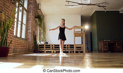 Young charming ballerina in black suit practicing in pirouette in dance studio. Beautiful slim girl dancing classic ballet in modern gym or ballroom