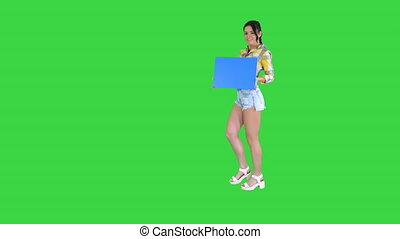Young charming brunette model holding empty board on a Green Screen, Blue mockup.