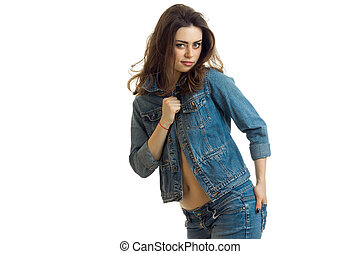 young charming brunette smiles and sexy poses for the camera in a jeans suit