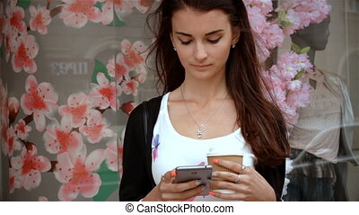 charming brunette stands in the street holding a coffee and looks at telephone