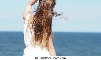 Young charming brunette woman on sea coast. Beautiful woman...