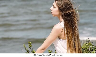 Young charming brunette woman on sea coast. Beautiful woman in white dress enjoys a wind, the feeling of freedom