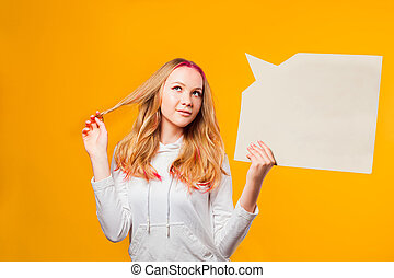 Young charming girl dreaming holding rectangular speaking cloud