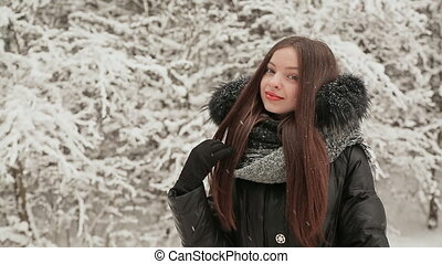 Young charming girl dressed in warm winter clothes posing near snow-covered fir trees. Smiling girl happy falling snow and winter.