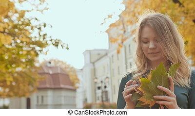 Young charming girl in dress is enjoying autumn in the park. She is holding a bouquet of autumn leaves.