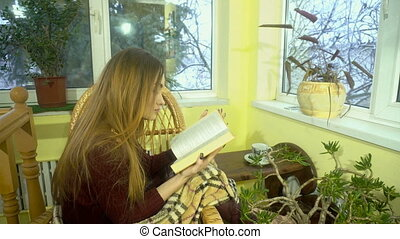 young charming girl sits in wicker chair read a book with snowfall behind the window