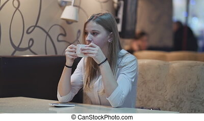 Young charming girl sitting at cafe while relaxing, drinking coffee from a cup and talking on the phone.