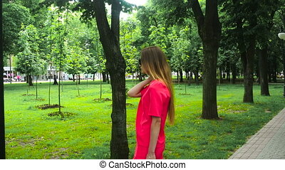 Young charming lady in red suit and black sunglasses posing in the park
