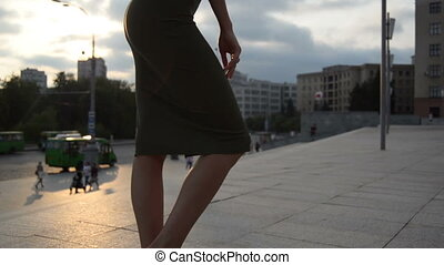 young charming lady in Slinky dress with sexy body stands on the street in the evening