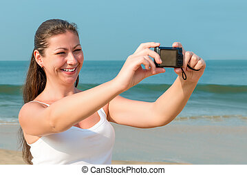 Young charming woman with a camera near the sea