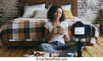 Young cheerful african american girl recording video blog...