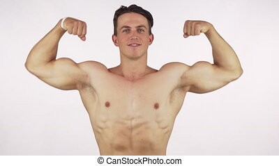 Young cheerful bodybuilder flexing his biceps, smiling to...