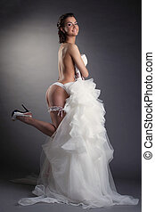 Young cheerful bride posing in white lingerie