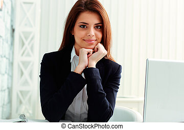 Young cheerful businesswoman sitting at the table on her workplace in office