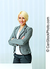 Young cheerful businesswoman standing with arms folded at office