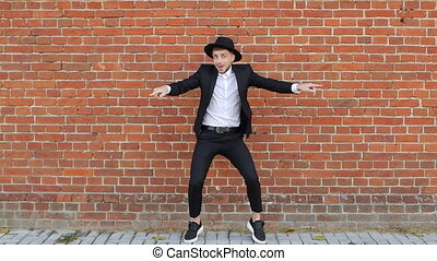Young cheerful caucasian man in a hat and black suit dances against a brick wall and takes off his hat, copy space, slow-mo