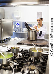 Young cheerful chef preparing meal