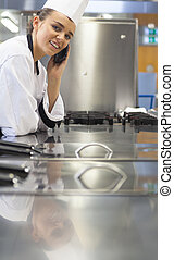 Young cheerful chef standing next